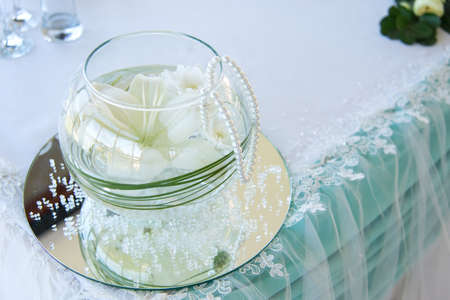 Wedding table decoration in a restaurant - glass sphere with white flowers, pearls and lace - selective focus