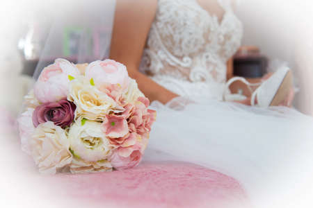 Beautiful bride in a wedding dress and bouquet of pink and white flowers.Selective focus. Text space. 스톡 콘텐츠