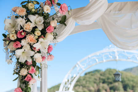 Wedding arch detail - pink and white flowers arranged with an ethereal veil against blue sky Stockfoto