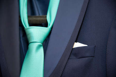 detail of a grooms dark blue costum eand a green tie  - selective focus, space for text