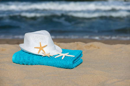 Summer vacation concept  towel with straw hat and starfish on sandy tropical beach - selective focus, copy space