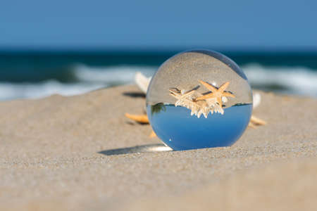 Lensball summer vacation landscape with starfish reflection. Travel and leasure concept. Selective focus, copy space.