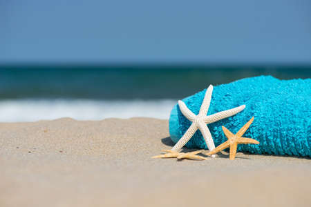 Summer vacation concept  towel with sunglasses and starfish on sandy tropical beach - selective focus, copy space