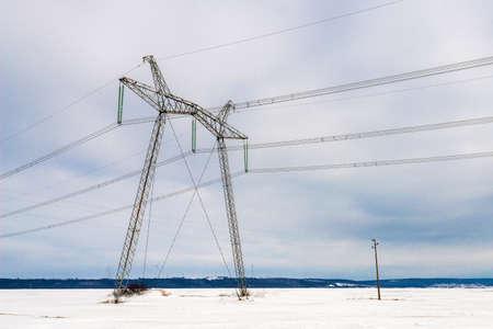 High voltage electric pillar against blue sky. Winter landscape.