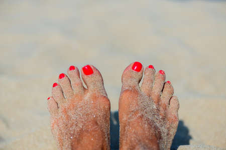 Summer vacation concept female feet with red lacquer on sand