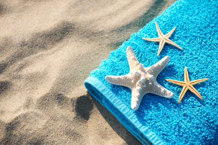 Summer vacation concept  towel with sunglasses and starfish on sandy tropical beach - top view, copy space