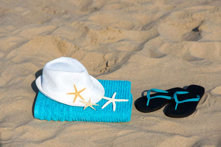 Summer vacation concept  towel with straw hat and starfish on sandy tropical beach