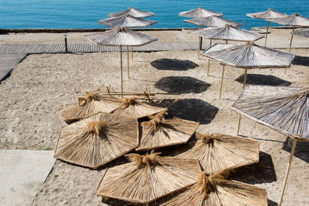 summer beach and straw umbrellas against blue sky and sea