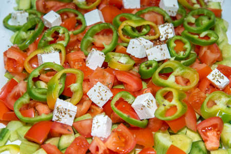 closeup of a salad made of tomatoes, cucumbers, peppers and cheese with spices