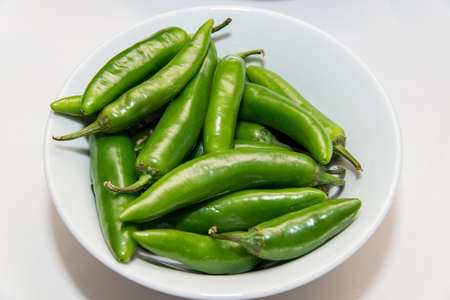 green hot peppers in a white plate over a  white background 版權商用圖片