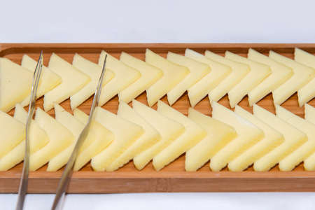 Catering food for the event - different types delicacies of meat and cheese arranged in wooden plate over white background - selective focus 版權商用圖片