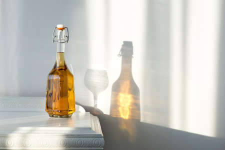 Elegant bottle with alcohol and empty glass over a vintage cabinet and a beautiful sun reflection on the wall - art concept Archivio Fotografico