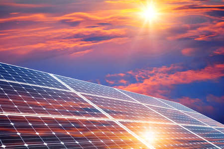 Photo collage of sunset and solar panel, photovoltaic, alternative electricity source - concept of sustainable resources