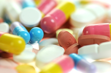 Colored capsules and tablets, close up photo