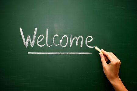 black board: Welcome handwritten in script in chalk on a blackboard