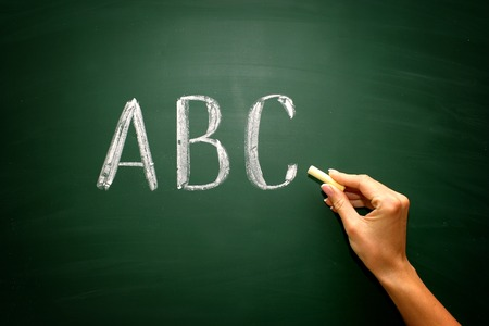 abc: abc letters with hand and chalk on blackboard