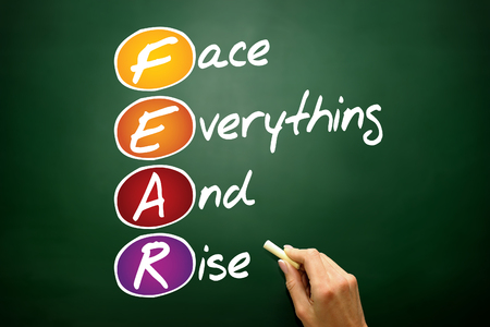 acronym: Face Everything And Rise (FEAR), business concept acronym on blackboard