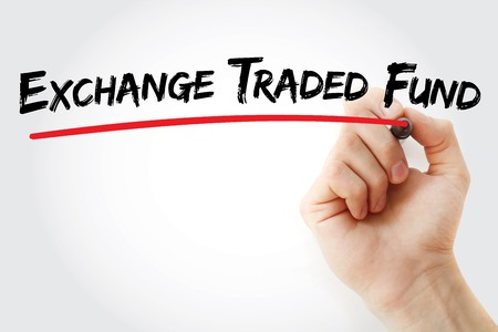 traded: Hand writing Exchange Traded Fund with marker, business concept background