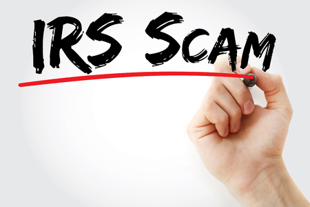 taxpayers: Hand writing IRS Scam with marker, concept background