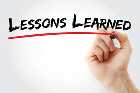 Main qui écrit les leçons apprises avec le marqueur, fond de concept Banque d'images