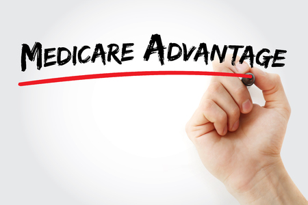 Hand writing Medicare Advantage with marker, concept background