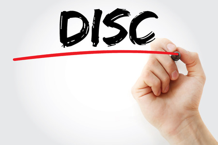 Hand writing DISC (Dominance, Influence, Steadiness, Conscientiousness) acronym - personal assessment tool to improve work productivity, business and education concept