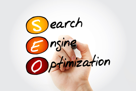 Hand writing SEO (Search Engine Optimization) with marker, business concept