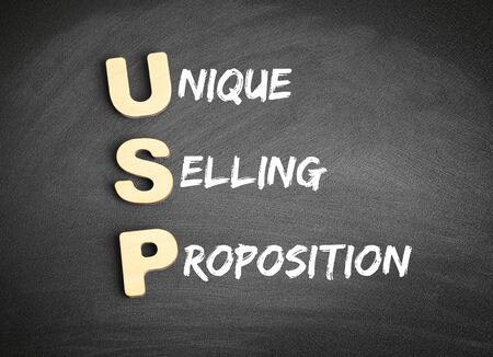 Wooden alphabets building the word USP - Unique Selling Proposition acronym on blackboard 스톡 콘텐츠
