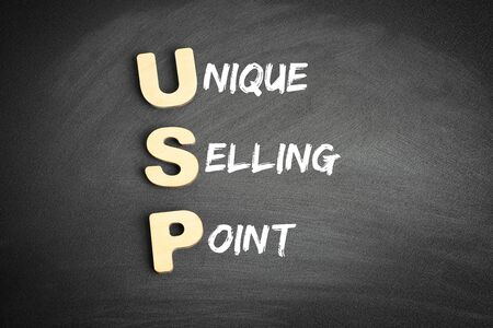 Wooden alphabets building the word USP - Unique Selling Point acronym on blackboard