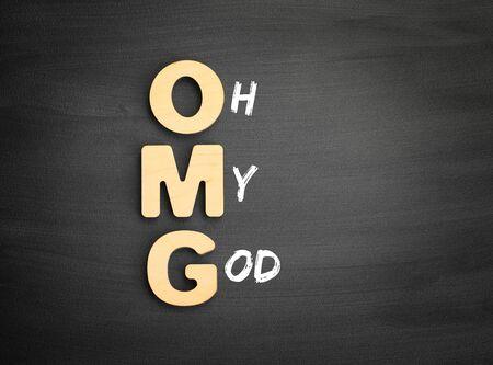 Wooden alphabets building the word OMG - Oh My God acronym on blackboard Фото со стока