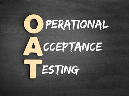 Wooden alphabets building the word OAT - Operational Acceptance Testing acronym on blackboard