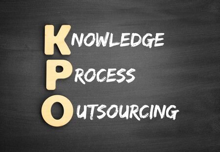 Wooden alphabets building the word KPO - Knowledge Process Outsourcing acronym on blackboard Фото со стока
