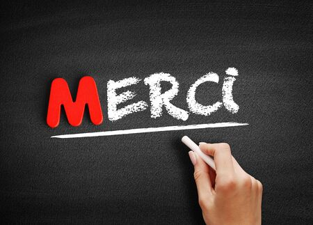Merci (Thank You In French) text on blackboard, business concept background