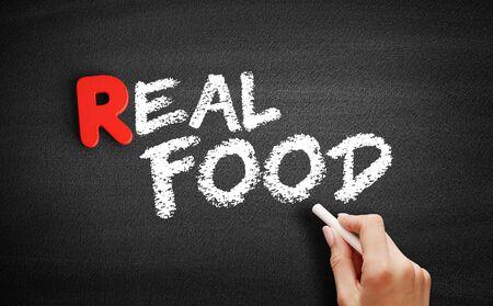 Real Food text on blackboard, business concept background Banco de Imagens