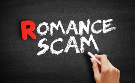 Romance scam text on blackboard, business concept background Banco de Imagens - 128458076
