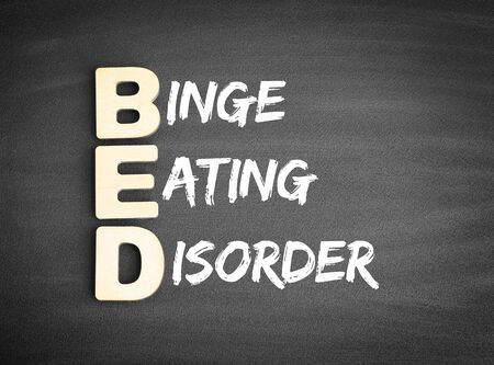 Wooden alphabets building the word BED - Binge Eating Disorder acronym on blackboard