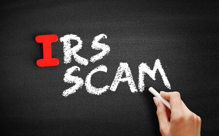 IRS Scam text on blackboard, technology concept background