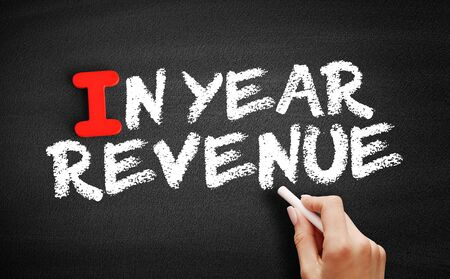 In Year Revenue text on blackboard, business concept background
