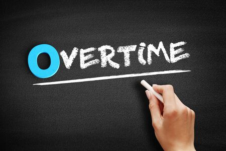 Overtime text on blackboard, business concept background
