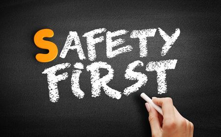 Safety First text on blackboard, business concept background