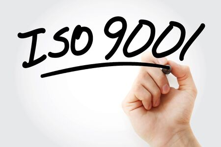 Hand writing ISO 9001 with marker, concept background