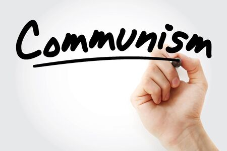 Hand writing Communism with marker, concept background