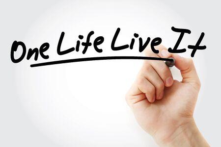 Main qui écrit One Life Live It avec marqueur, arrière-plan concept