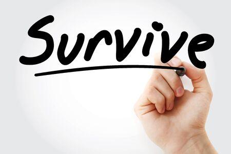 Main qui écrit Survivre avec le marqueur, arrière-plan du concept de santé Banque d'images