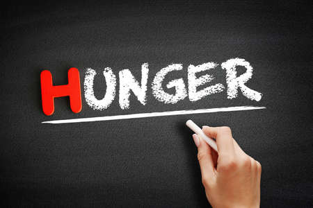 Hand writing hunger on blackboard, concept background