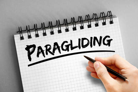 Paragliding text on notepad, concept background Imagens