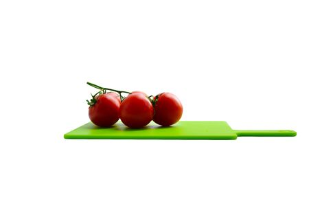 garden stuff: raw tomato on kitchen cut board isolated over white background