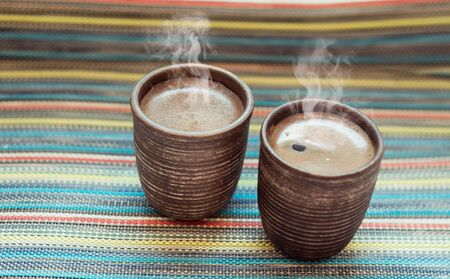 hot coffees: two clay cups with coffee on the color background