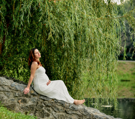 warm weather: cute pregnant woman sitting in the park. on background the sunset warm weather