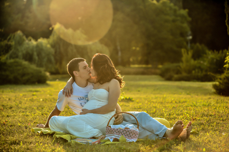 Happy pregnant couple sitting on the grass in the park Stock Photo